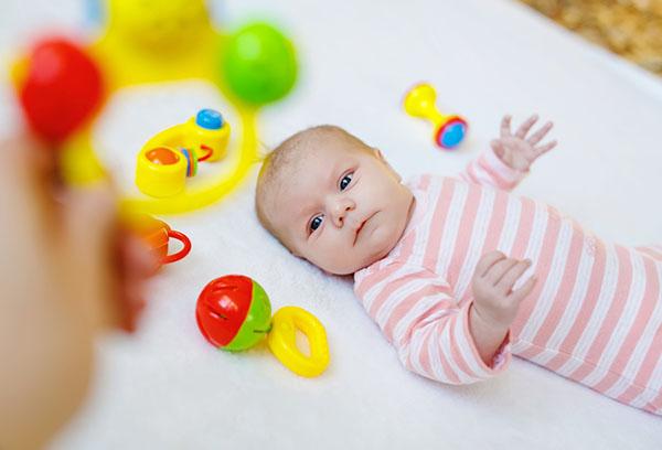 Новорожденный малыш с погремушками