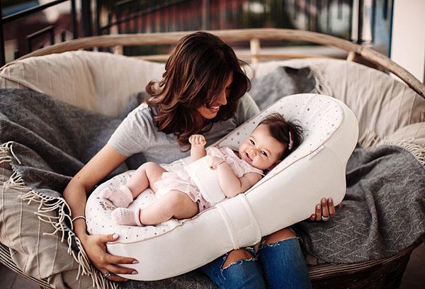 Мама держит малыша в люльке