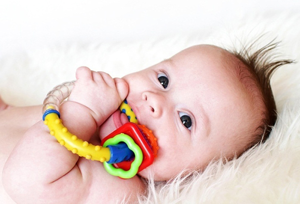 Младенец грызет игрушку-прорезыватель