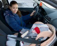 Женщина за рулем и младенец в автокресле