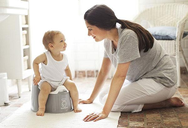 Мама разговаривает с малышом, сидящем на горшке