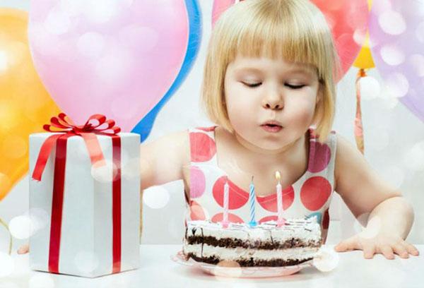 Девочка задувает свечи на торте