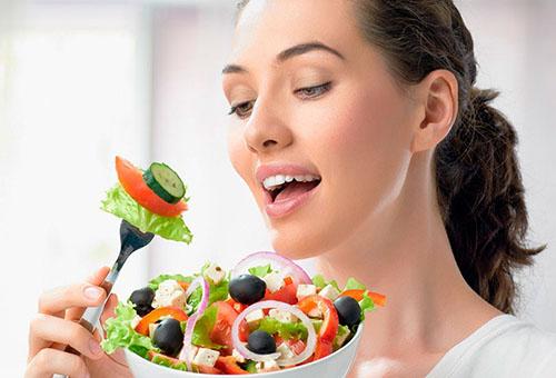 Молодая женщина ест овощной салат с огурцом