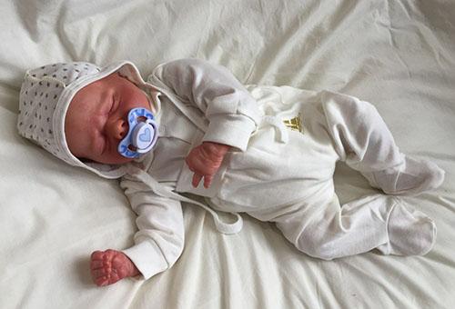 Спящий новорожденный, одетый для летней прогулки