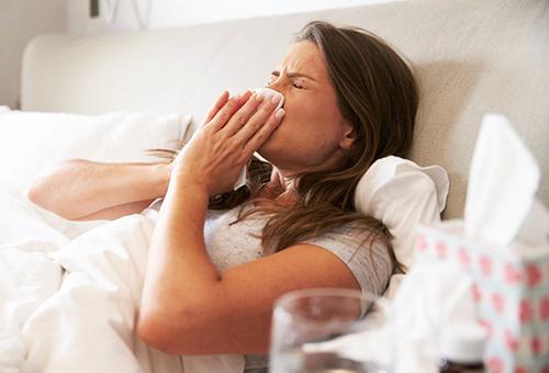 Молодая женщина болеет простудой