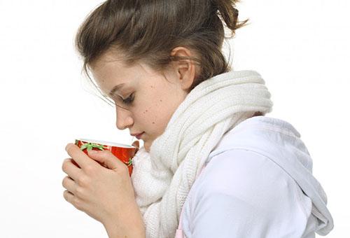 Девушка пьет теплый чай при ангине
