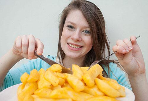 Женщина ест жареную картошку