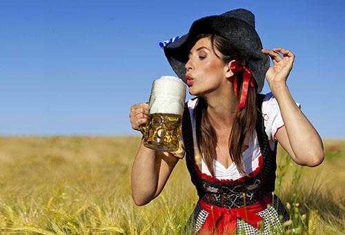 Женщина пьет пиво в поле