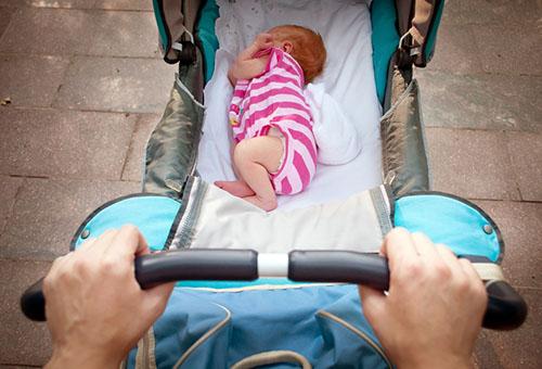 Новорожденная девочка в коляске на прогулке