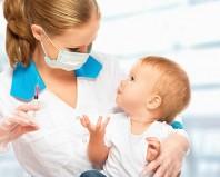 Педиатр готовится сделать прививку малышу