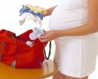 Беременная укладывает вещи в сумку