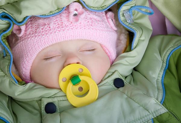 Спящая новорожденная девочка в осенней одежде
