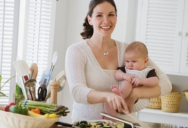 Молодая мама с грудничком в кухне