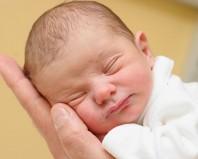 Новорожденный спит на руках