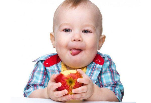 Мальчик кушает яблоко