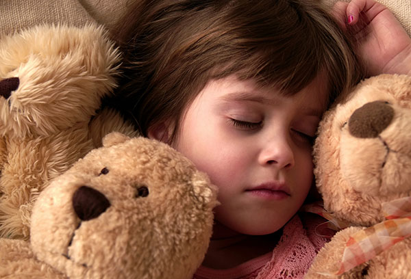 Девочка спит с игрушками