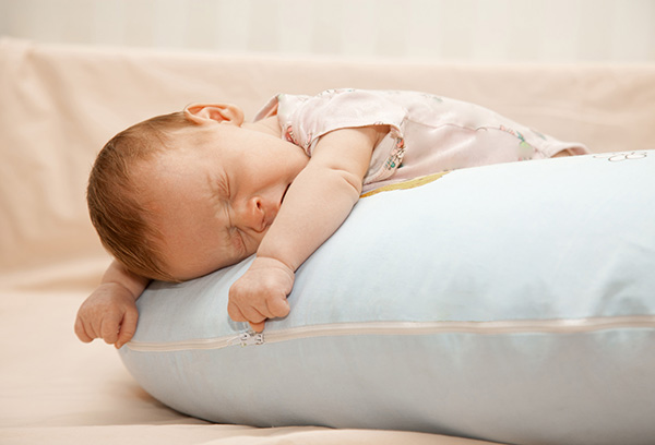 Восьмимесячный ребенок засыпает на подушке