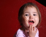 Девочка тянет руки в рот