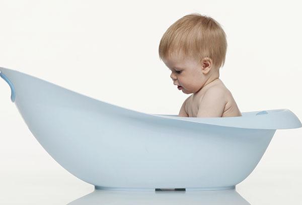 Маленький мальчик в детской ванночке