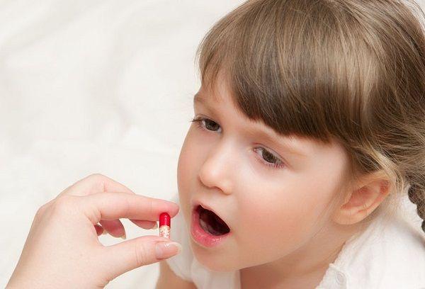 девочка пьет таблетку