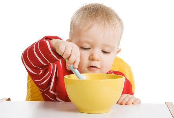 ребенок ест фруктовое пюре