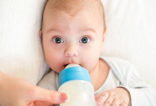 новорожденный ребенок ест с бутылочки