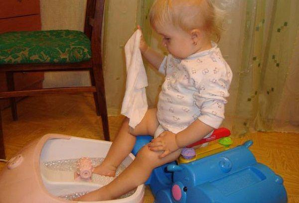 ребенок выпаривает ноги в тазике