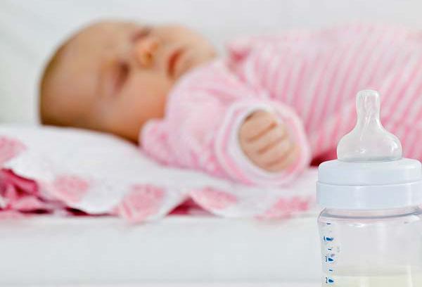Спящий малыш и бутылочка с детским питанием