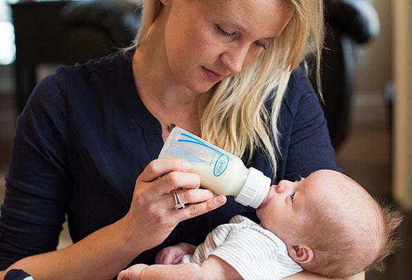 Женщина кормит новорожденного из бутылочки