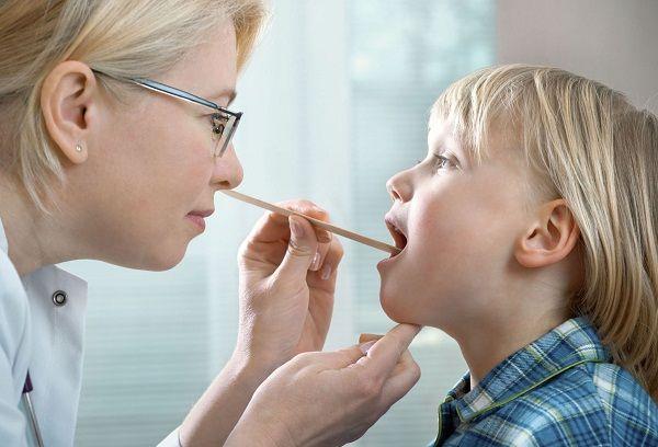 врач осматривает горло мальчика