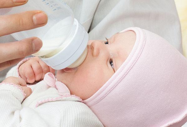 Ребенок в чепчике ест из бутылочки