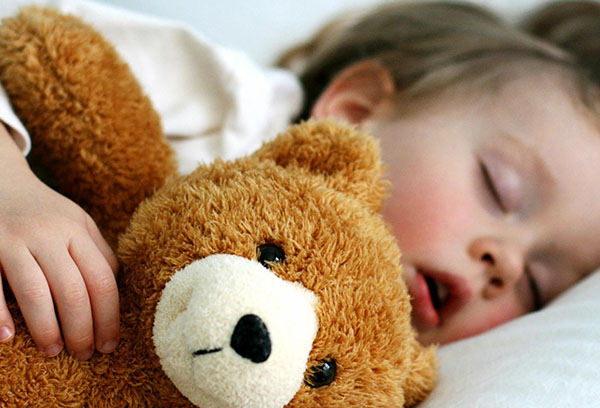 Ребенок спит с плюшевым мишкой
