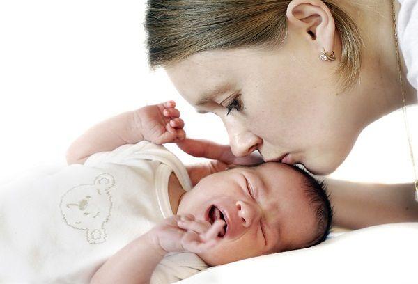 мама успокаивает плачущего грудничка