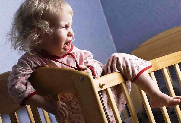 девочка плачет в кроватке