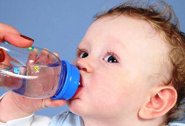 Маленький ребенок пьет воду из бутылочки