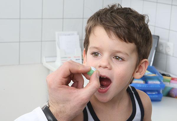 Врач дает таблетку ребенку