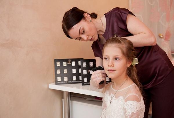 девочка на процедуре прокалывания ушей