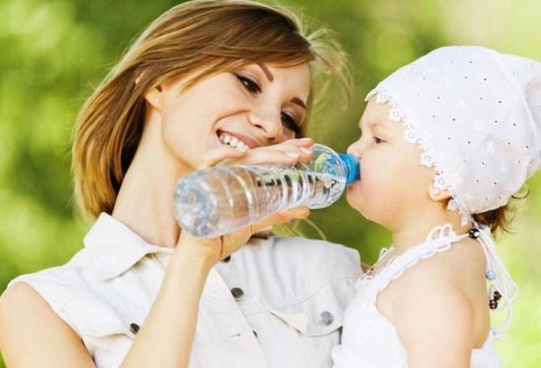 малыш пьет воду из бутылки
