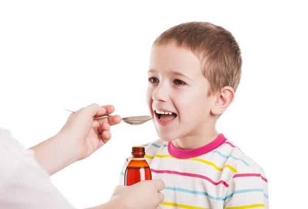 улыбающийся мальчик принимает лекарственный сироп из ложки