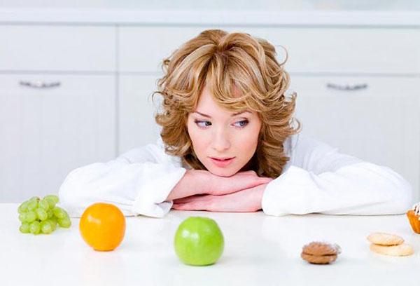 Женщина выбирает между фруктами и сладостями