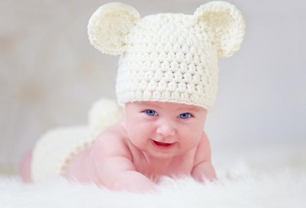 новорожденный ребенок в белой шапке