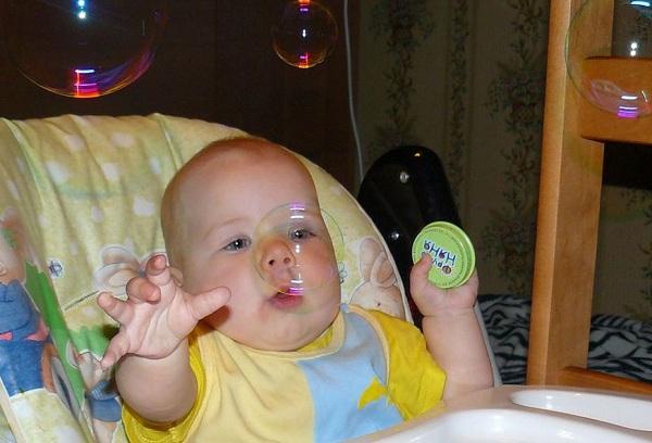 ребенок играет с мыльшыми пузырями