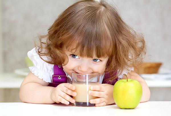 Маленькая девочка пьет яблочный сок