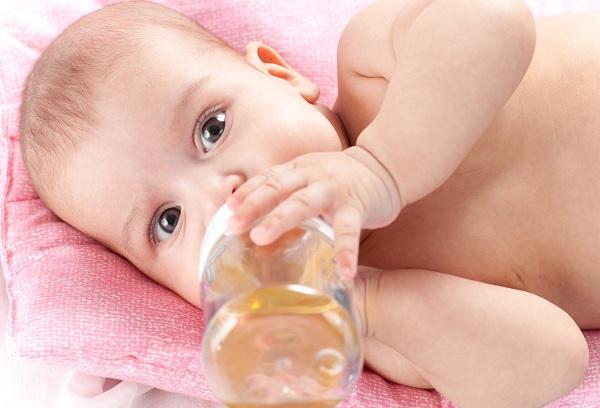 грудничок пьет из бутылки