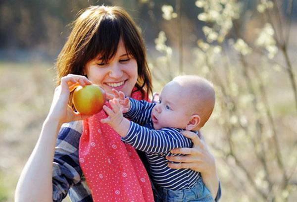 Малыш тянется за яблоком