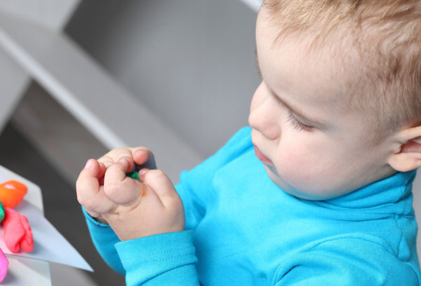Двухлетний малыш лепит из пластилина