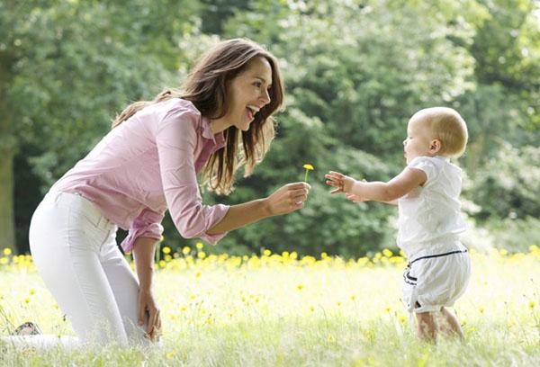 Мама протягивает одуванчик малышу
