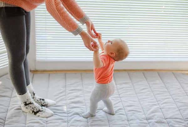 Женщина учит малыша ходить