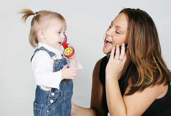 Мама с дочкой играет в телефон