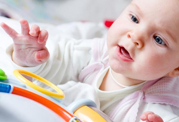 9-месячный ребенок тянется к игрушке
